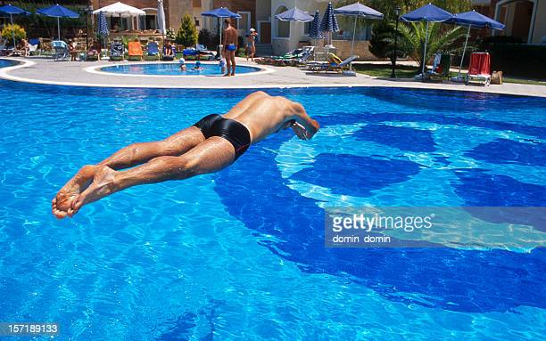 Young man jumping into the hotel's pool located on backyard