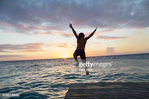 Young man jumping into water at sunset : ストックフォト