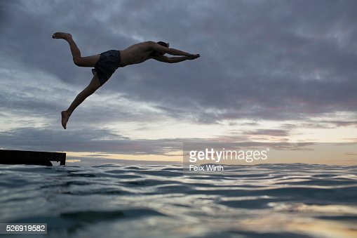 Young man jumping into water at sunset : Stockfoto