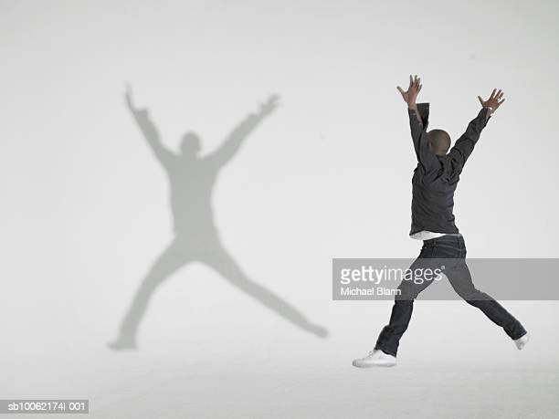 Young man jumping, making shadow on white background