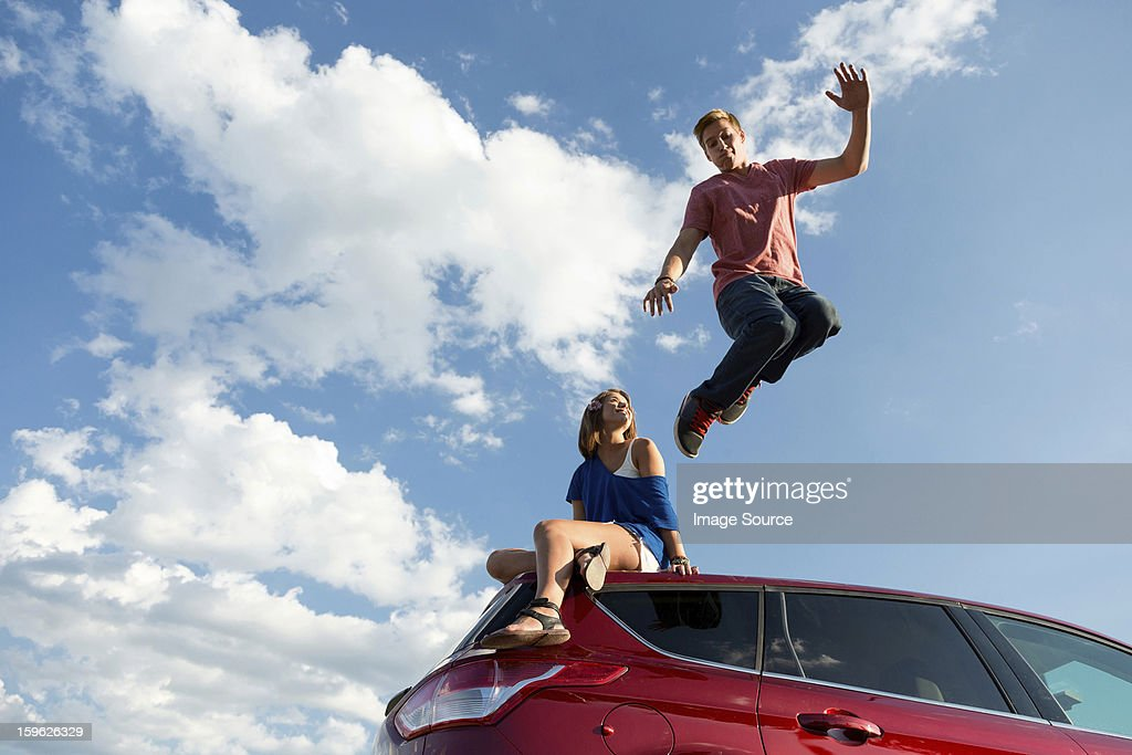 young man jumping off car roof girl sitting on roof stock photo getty images. Black Bedroom Furniture Sets. Home Design Ideas