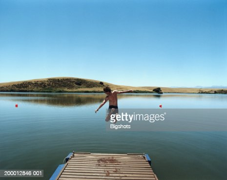 Young man jumping off jetty into lake : Stock Photo