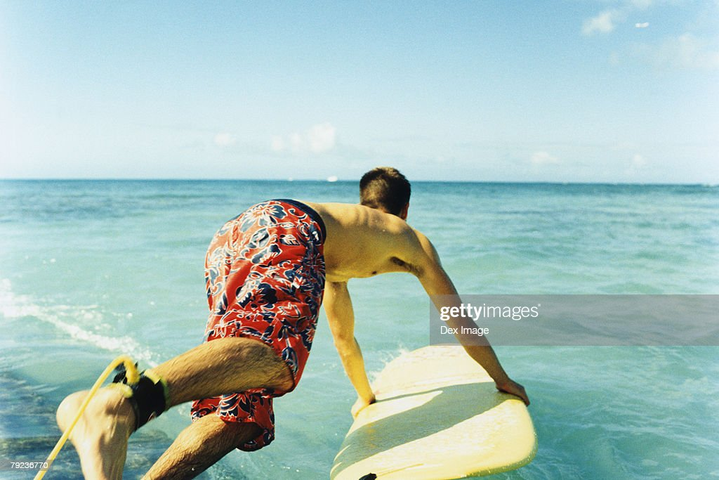 Young man jumping off with surfboard, rear view : Stock Photo
