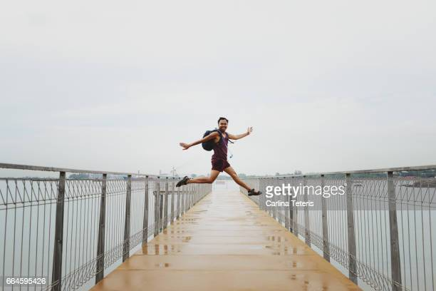 Young man jumping on a jetty on a rainy day