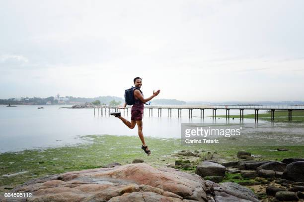 Young man jumping on a rock in front of a grassy intertidal flat