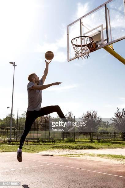 若者のバスケット ボールのコート上でジャンプ