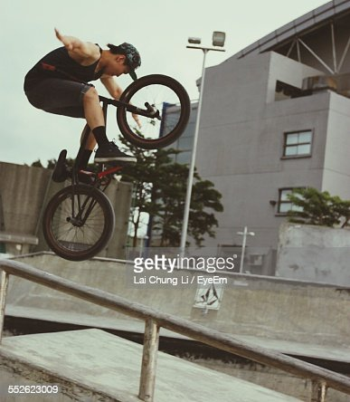 Young Man Jumping On Bicycle