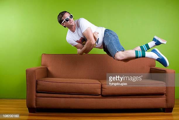 Young Man Jumping Onto Sofa,