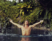 Young man jumping out of water with outstretched arms, eyes closed