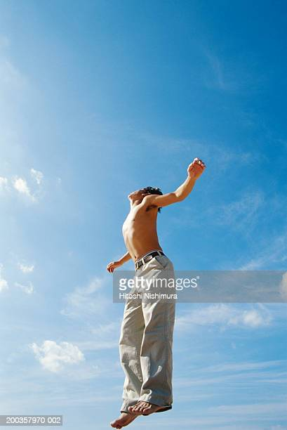 Young man jumping outdoors, low angle view