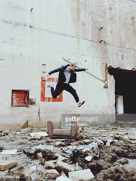 Young Man Jumping Over Chair Outside Abandoned Building