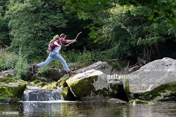 Jovem saltar sobre o rio