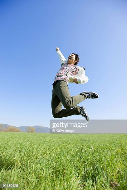 Young man jumping, raising fist, in green field