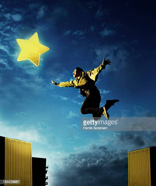 young man  jumping to catch starshaped gaming icon