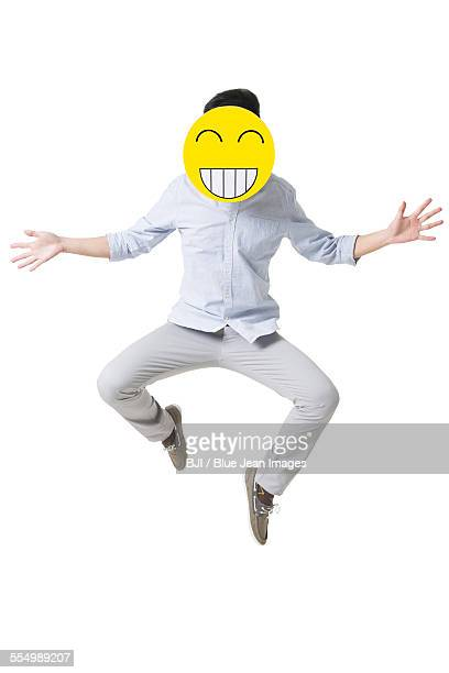 Young man jumping with a happy emoticon face in front of his face