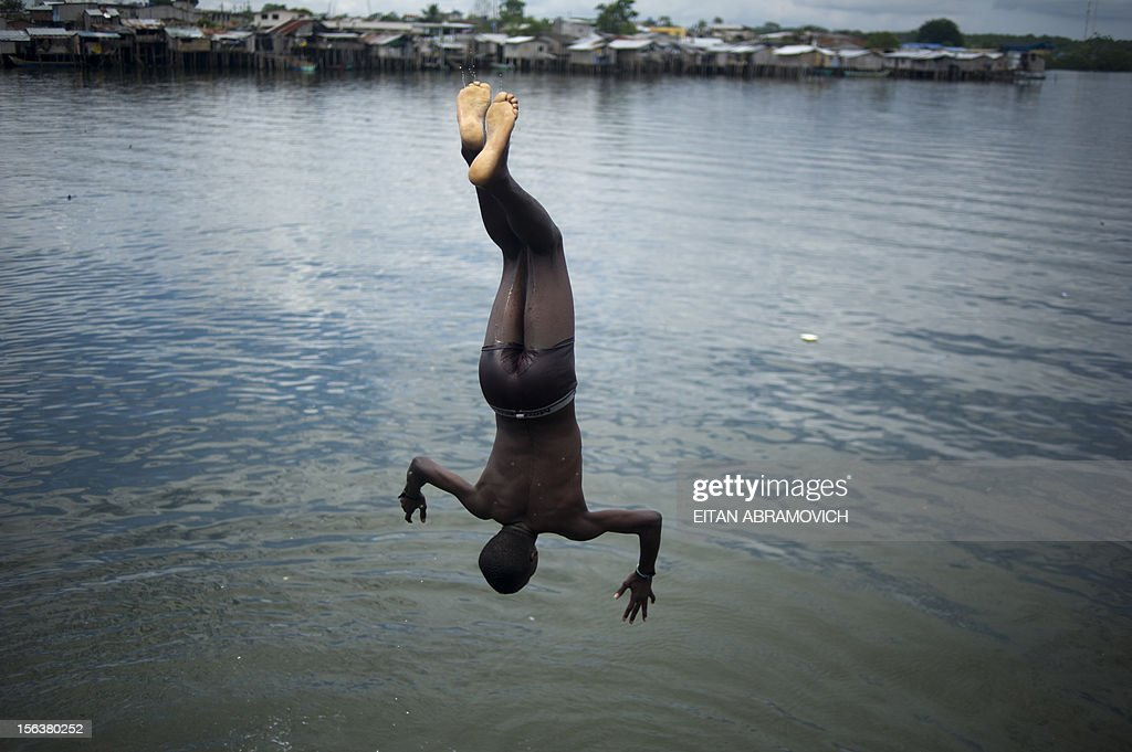 A young man jumps from the pier of the port of San Lorenzo, Esmeraldas province, in northwestern Ecuador, near the border with Colombia, on November 8, 2012. AFP PHOTO/Eitan Abramovich