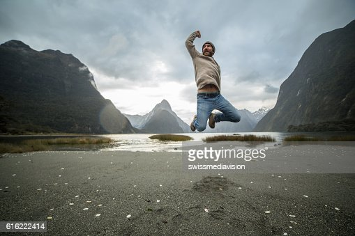 Young man jumps in front of Mitre peak, New Zealand : Stock Photo