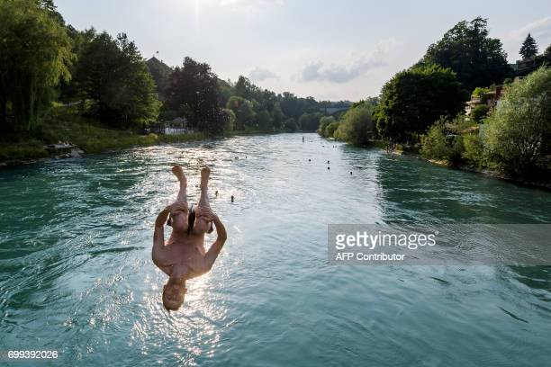 A young man jumps into the river Aare on June 21 2017 in Bern Europe sizzled in a continentwide heatwave with London bracing for Britain's hottest...