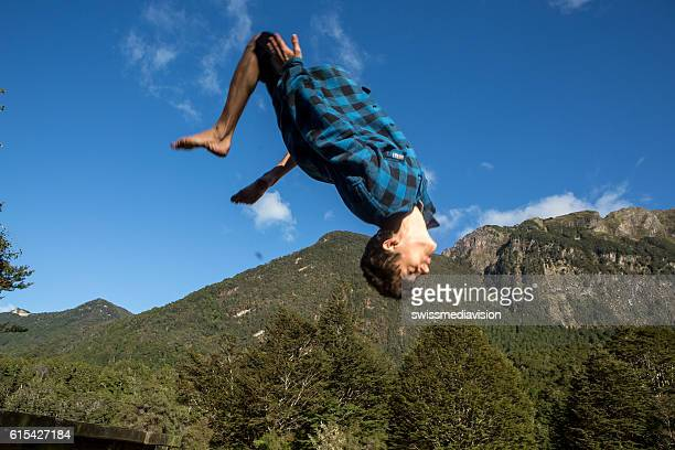 Young man jumps mid-air against blue sky