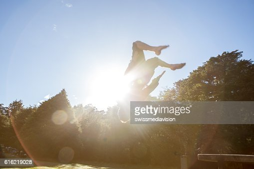 Young man jumps mid-air against blue sky : Stock Photo