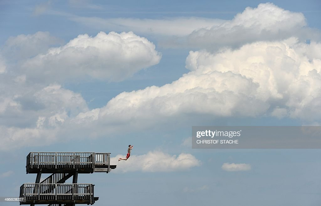 A young man jumps off a diving platform at lake Ammersee in Utting, southern Germany, on June 4, 2014, a day with summer-like temperatures. Meteorologists forecast a warm and sunny weekend for the southern German region.