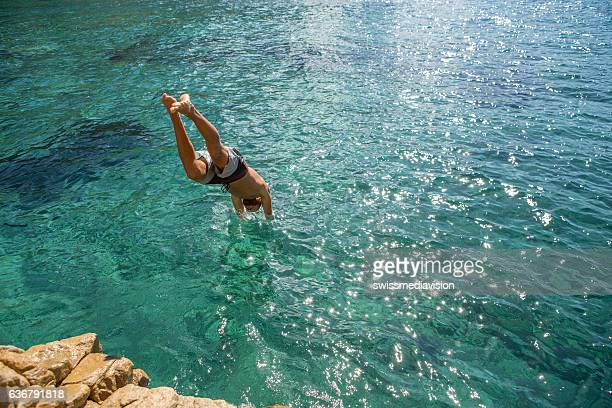 Young man jumps off the cliff into the sea