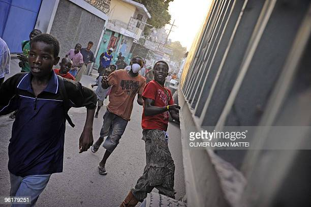 A young man jumps on a truck distributing water January 25 2010 in a street of PortauPrince Donor nations rallied behind Haiti promising to pour...