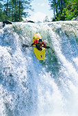 Young man kayaking down steep waterfall