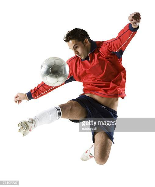 Young man kicking a soccer ball
