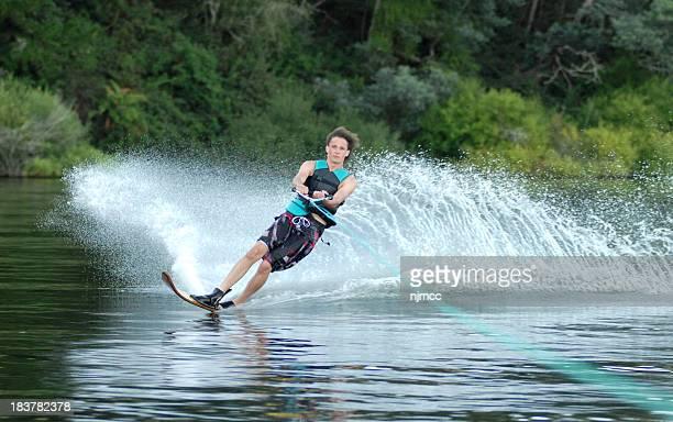 young man kicking up spray on water ski