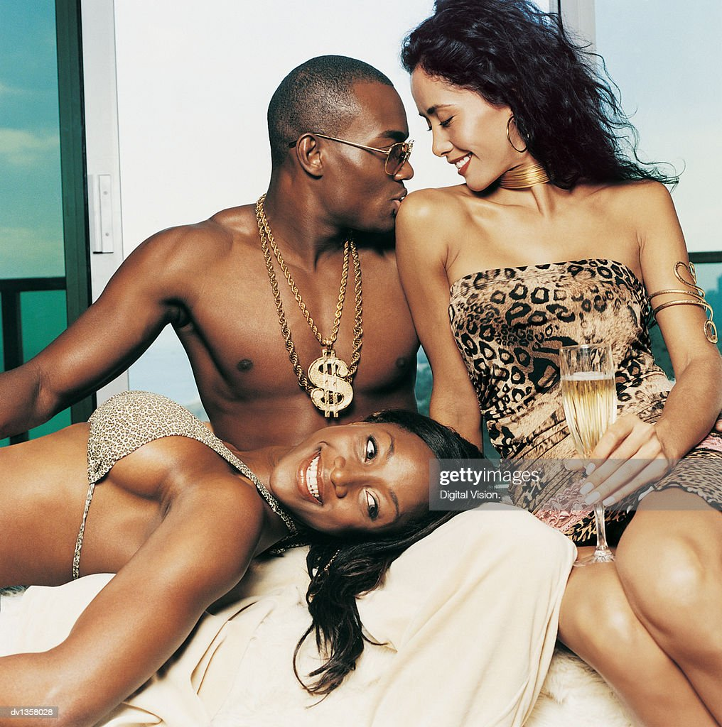 Young Man Kissing a Young Woman Sitting on a Sofa by Another Young Woman Lying Down : Stock Photo