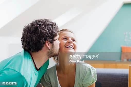 Young man kissing girl on cheek : Stock Photo