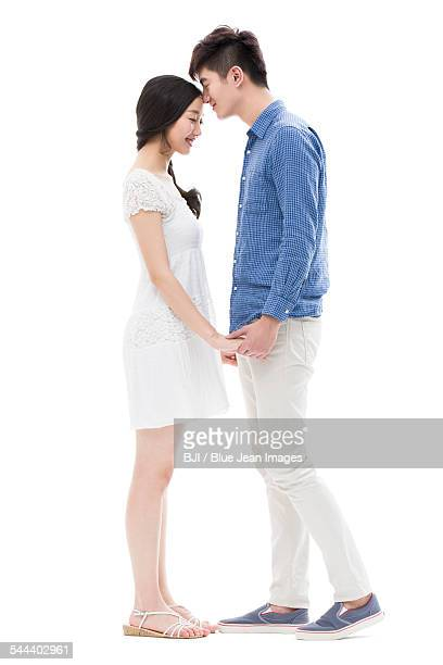 Young man kissing girlfriend on forehead