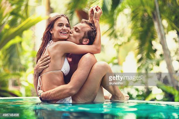 Young man kissing hid girlfriend in infinity pool.