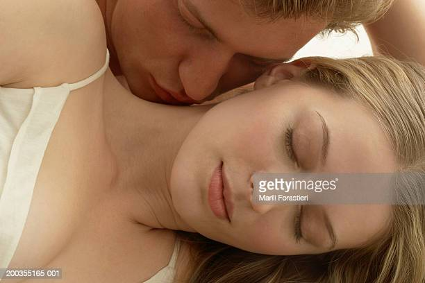 Young man kissing woman on neck, close-up