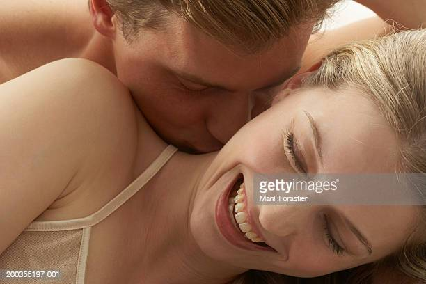 Young man kissing woman's neck, close-up