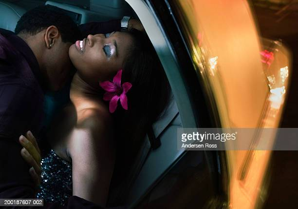 Young man kissing young woman in back seat of car, night