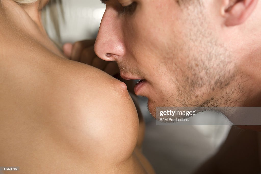 Man kissing naked boobs