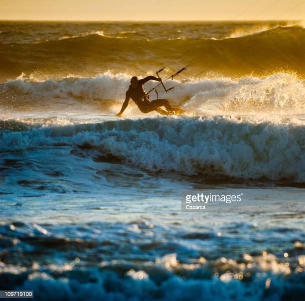 Junger Mann Kitesurfen im Ozean Wellen bei Sonnenuntergang
