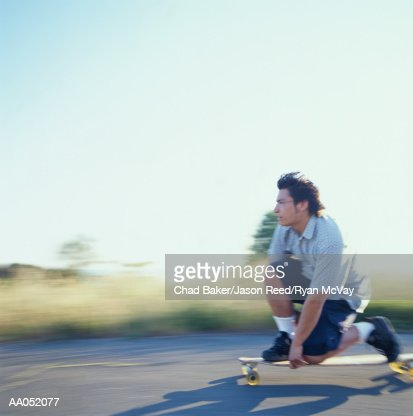 Young man kneeling down on longboard, side view (blurred motion) : Bildbanksbilder