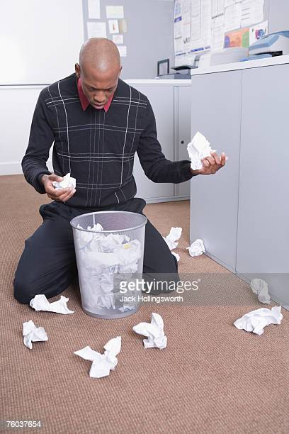 Young man kneeling in office, looking for paper in trash can