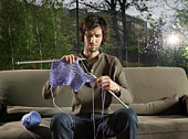 Young man knitting on sofa in livingroom