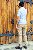 Young man knocking on closed wooden church door.