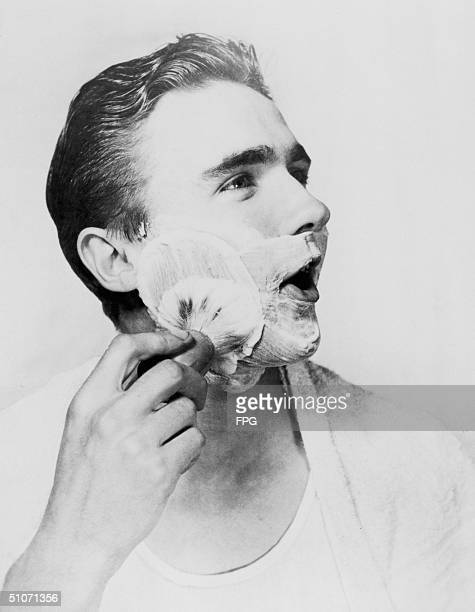 A young man lathers up his face with a shaving brush circa 1950