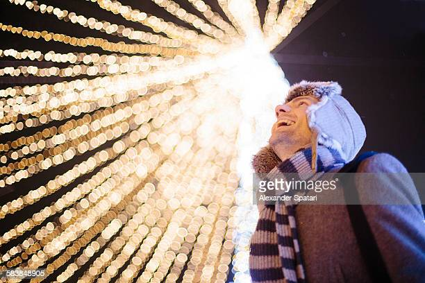 Young man laughing against Christmas lights