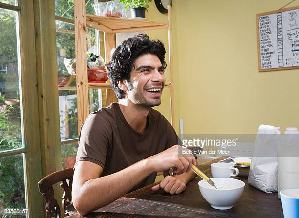 Young man laughing at breakfast table.