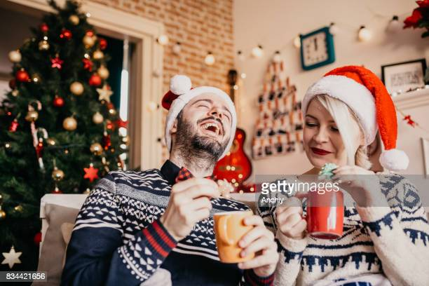 Young man laughing on his girlfriend joke, while eating Christmas cookies