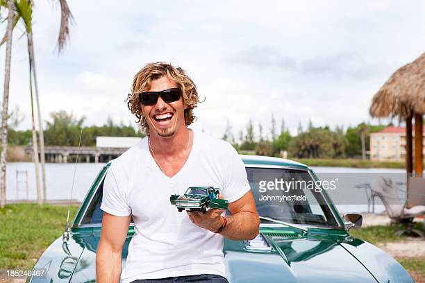 Young man laughing with car