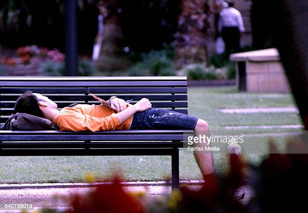 A young man laying on a park bench
