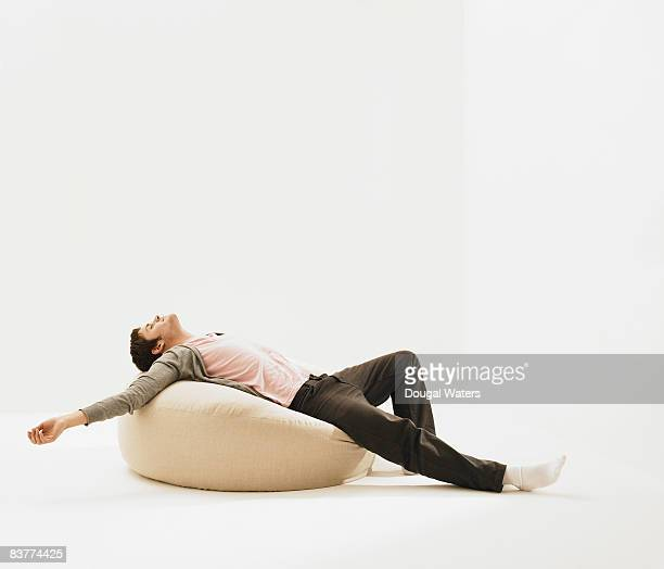Young man laying on beanbag.